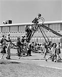 1950s ELEMENTARY SCHOOL PLAYGROUND AT RECESS WITH LINE OF CHILDREN CLIMBING LADDER OF SLIDE