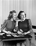 1940s TWO GIRLS SITTING AT CARD TABLE PLAYING CARDS AND WHISPERING    Stock Photo - Premium Rights-Managed, Artist: ClassicStock, Code: 846-02797461