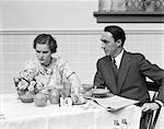 1930s QUARRELING COUPLE AT A TABLE SET FOR BREAKFAST THE WOMAN IS WEARING PRINT DRESS BOW