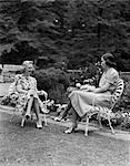 1940s TWO WOMEN SITTING IN LAWN CHAIRS TALKING SMILING BACKYARD GARDEN BOTH WEARING COTTON PRINT DRESS AND SPECTATOR SHOES