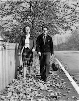 1930s TEEN COUPLE WALKING ON SIDEWALK IN FALL GIRL CARRYING SCHOOLBOOKS BOY CARRYING FOOTBALL AND LEATHER HELMET SMILING OUTDOOR    Stock Photo - Premium Rights-Managednull, Code: 846-02797517
