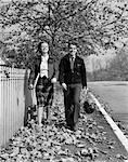 1930s TEEN COUPLE WALKING ON SIDEWALK IN FALL GIRL CARRYING SCHOOLBOOKS BOY CARRYING FOOTBALL AND LEATHER HELMET SMILING OUTDOOR