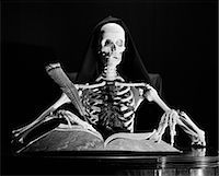 STILL LIFE OF SKELETON WRITING IN LARGE BOOK WITH QUILL PEN    Stock Photo - Premium Rights-Managednull, Code: 846-02797518