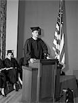 1950s VALEDICTORIAN GIVING SPEECH AT PODIUM WITH OTHER GRADUATES SEATED IN BACKGROUND HOLDING DIPLOMAS