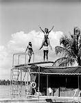 1930s GIRL ON BOY'S SHOULDERS WITH ARMS IN AIR GIRL STANDING ON DIVING BOARD NEAR SWIMMING POOL