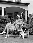 1940s WOMAN HOLDING BOOK SMILING AT CAMERA SITTING IN LAWN CHAIR MAGAZINE RACK PORCH HOUSE