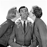 1950s TWO WOMEN KISSING SINGLE MAN ON OPPOSITE CHEEKS HIS FACE COVERED WITH LIPSTICK MARKS    Stock Photo - Premium Rights-Managednull, Code: 846-02797551