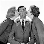 1950s TWO WOMEN KISSING SINGLE MAN ON OPPOSITE CHEEKS HIS FACE COVERED WITH LIPSTICK MARKS    Stock Photo - Premium Rights-Managed, Artist: ClassicStock, Code: 846-02797551