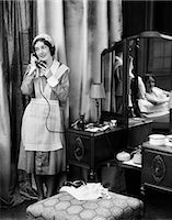 1920s 1930s MAID IN UNIFORM TALKS ON TELEPHONE IN FRONT OF VANITY DRESSING TABLE OTHER WOMAN IS SEEN AS REFLECTION IN MIRROR    Stock Photo - Premium Rights-Managednull, Code: 846-02797628