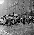 1950s PEDESTRIANS INTERSECTION CITY CROSS WALK UMBRELLAS RAIN WEATHER WET TROLLEY CAR PHILADELPHIA