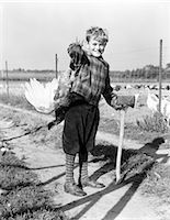 1940s BOY IN PLAID JACKET AND KNICKERS SMILING HOLDING LIVE TURKEY OVER SHOULDER AND AXE    Stock Photo - Premium Rights-Managednull, Code: 846-02797660