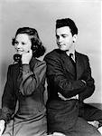 1930s 1940s YOUNG COUPLE GIRL TALKING ON TELEPHONE BOY ARMS CROSSED LOOKS ANNOYED    Stock Photo - Premium Rights-Managed, Artist: ClassicStock, Code: 846-02797715