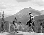 1930s HORSEMEN ONE IN BOOTS JODHPURS & WOOL HUNTING SHIRT STANDING NEXT TO MOVIE CAMERA ON TRIPOD OTHER IS MOUNTED COWBOY