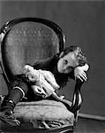 1930s GIRL IN TATTERED CLOTHING SITTING HOLDING BABY DOLL LEANING HEAD ON ARM OF CHAIR WITH SAD EXPRESSION