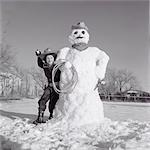 1950s BOY DRESSED LIKE COWBOY THROWING SNOWBALL FROM BEHIND SNOWMAN