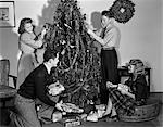 1930s 1940s FAMILY DECORATING CHRISTMAS TREE PUTTING WRAPPED GIFTS UNDER TREE