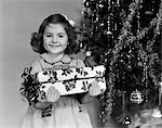 1940s LITTLE GIRL STANDING NEAR CHRISTMAS TREE HOLDING A WRAPPED PRESENT SMILING