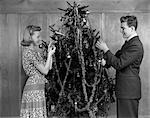 1930s 1940s COUPLE DECORATING CHRISTMAS TREE WITH TINSEL AND ORNAMENTS