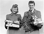 1930s 1940s COUPLE IN WINTER COATS HOLDING PACKAGES AND WREATH MADE OF PINE CONES