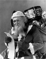 1930s SANTA WITH SACK OF TOYS OVER BACK CHECKING HIS LIST    Stock Photo - Premium Rights-Managednull, Code: 846-02797879