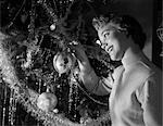 1950s SMILING PRETTY YOUNG WOMAN HANGING GLASS CHRISTMAS ORNAMENT ON BRANCH LIGHT COMES FROM THE TREE