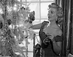 1950s WOMAN DECORATING CHRISTMAS TREE WITH FESTIVE GLASS BALLS