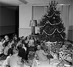 1950s SEATED GROUP OF 20 CHILDREN LOOKING UP AT CHRISTMAS TREE DECORATED WITH POPCORN AND STARS