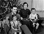 1940s 1950s FAMILY SITTING AROUND CHRISTMAS TREE HOLDING GIFTS