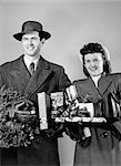 1940s COUPLE STANDING IN WINTER COATS HOLDING WRAPPED GIFTS AND A WREATH STUDIO