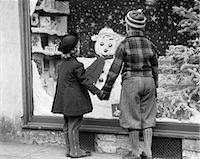 1930s BOY AND GIRL HOLDING HANDS LOOKING AT DECORATED CHRISTMAS WINDOW    Stock Photo - Premium Rights-Managednull, Code: 846-02797920