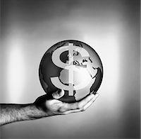 Man holding globe with dollar symbol Stock Photo - Premium Royalty-Freenull, Code: 635-02800556