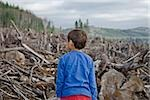Young boy looking out at cleared landscape of fallen trees Stock Photo - Premium Royalty-Freenull, Code: 673-02801435