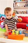 Boy with Down Syndrom Sitting on Floor and Playing with Toy Stock Photo - Premium Rights-Managed, Artist: SimplyMui, Code: 700-02833638
