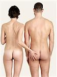 Rear view of a naked woman touching a naked man's bottom