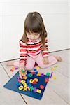 Girl playing with magnets Stock Photo - Premium Royalty-Free, Artist: Ikon Images, Code: 614-02838007