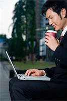 A man has a coffee as he sits and uses his laptop outdoors Stock Photo - Premium Rights-Managednull, Code: 849-02860902