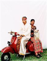 Indonesia, Bali, Ubud, Balinese wedding couple in ceremonial dress, sitting on motor scooter, woman carrying offering. Stock Photo - Premium Rights-Managednull, Code: 849-02867618