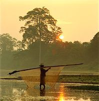Cambodia, Sien Reap, Angkor Wat, Local woman carrying fishing net across river at dawn Stock Photo - Premium Rights-Managednull, Code: 849-02874950
