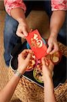 Close up of two pairs of hands, exchanging red packets Stock Photo - Premium Rights-Managed, Artist: Asia Images, Code: 849-02876428