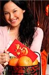 Woman with basket of oranges and red packet, smiling Stock Photo - Premium Rights-Managed, Artist: Asia Images, Code: 849-02876534