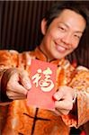 Man in traditional Chinese clothing holding red packet Stock Photo - Premium Rights-Managed, Artist: Asia Images, Code: 849-02876544
