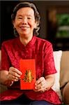 Senior woman holding red packet, smiling Stock Photo - Premium Rights-Managed, Artist: Asia Images, Code: 849-02876602