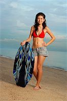 Young woman on beach, standing next to skimboard Stock Photo - Premium Rights-Managednull, Code: 849-02877809