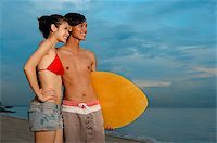 Couple standing on beach, man carrying skimboard, looking away Stock Photo - Premium Rights-Managednull, Code: 849-02877817