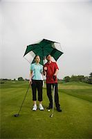 Father and Daughter on the Golf Course Holding a Large Umbrella Stock Photo - Premium Royalty-Freenull, Code: 600-02883090
