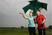 Father and Daughter on the Golf Course Holding a Large Umbrella Stock Photo - Premium Royalty-Freenull, Code: 600-02883091