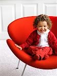 Little Girl in White and Red Outfit Sitting on a Red Chair in a White Room Stock Photo - Premium Rights-Managed, Artist: Yvonne Duivenvoorden, Code: 700-02883259