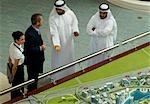 High angle view of man and woman discussing property with men in traditional Middle Eastern dress, Dubai, UAE
