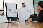 Man dressed in Middle Eastern traditional dress giving presentation to businessmen, Dubai, UAE