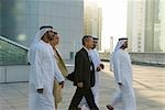 Businessman and woman walking with men dressed in traditional Middle Eastern attire, Dubai cityscape in background, UAE
